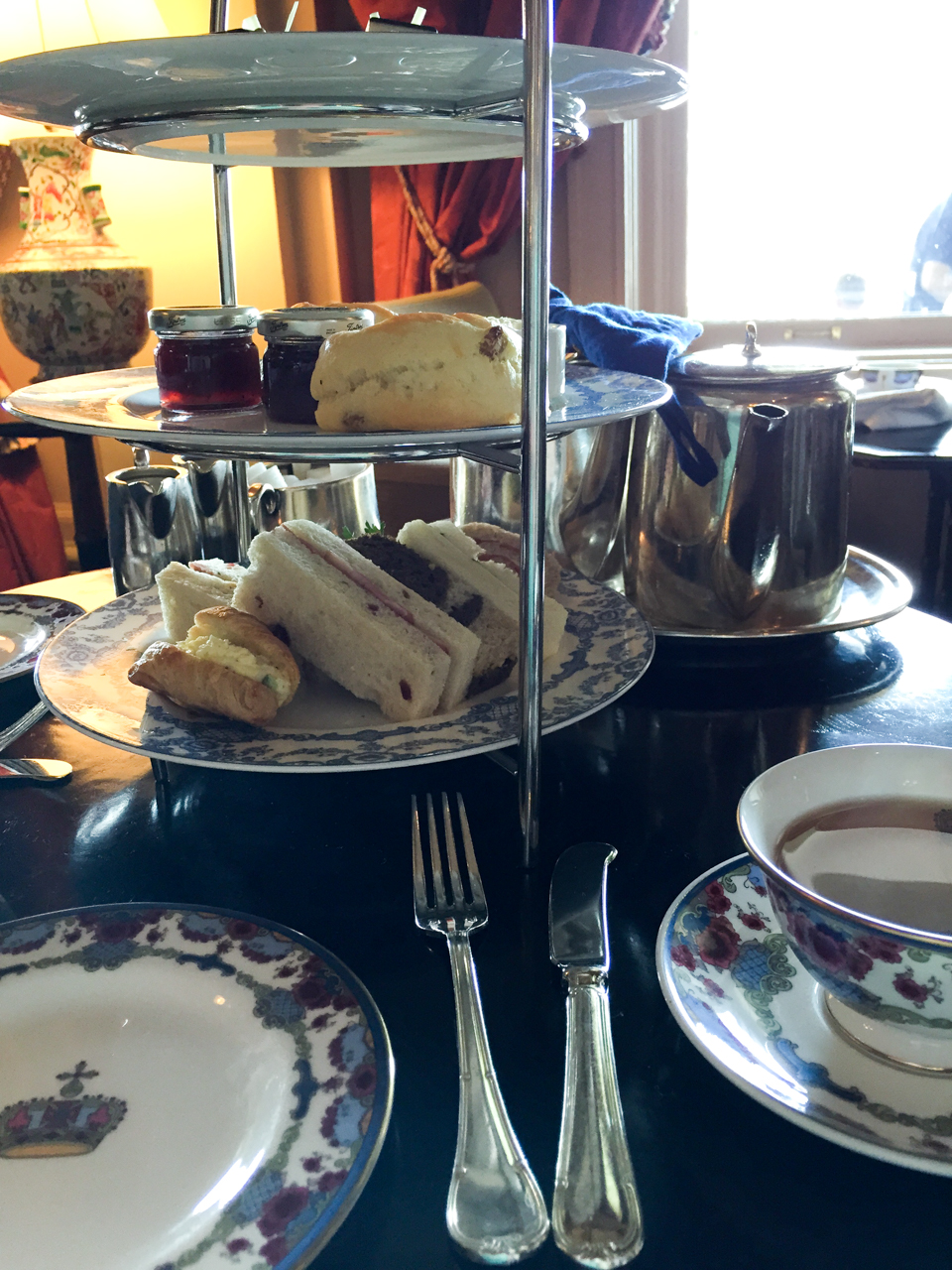 A three-tier servers holds bite-sized treats, scones with heavy cream and jam, and finger sandwiches--at The Empress afternoon tea.