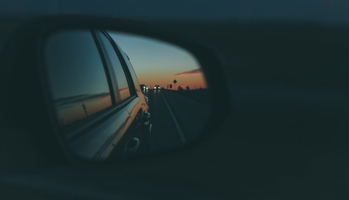 A car's side view mirror shows a sunset.