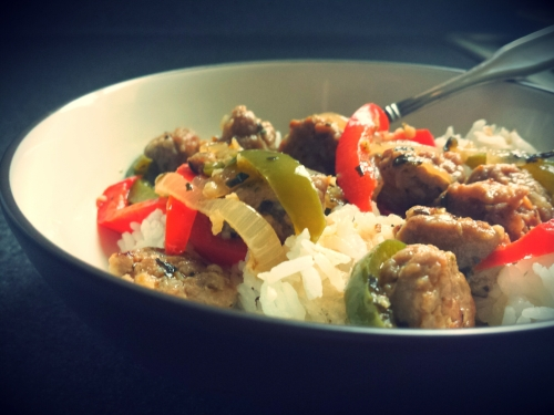 A bowl of sausage, peppers, and onions over rice.