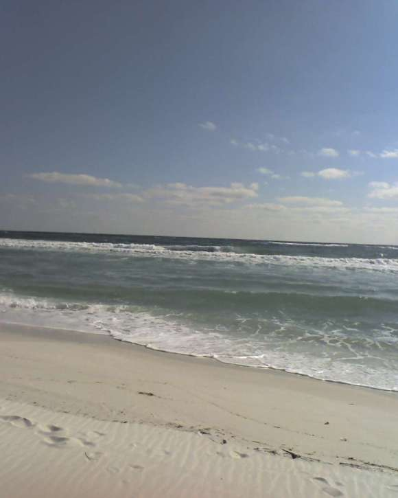 Waves lap onto to the shore of a sandy beach.