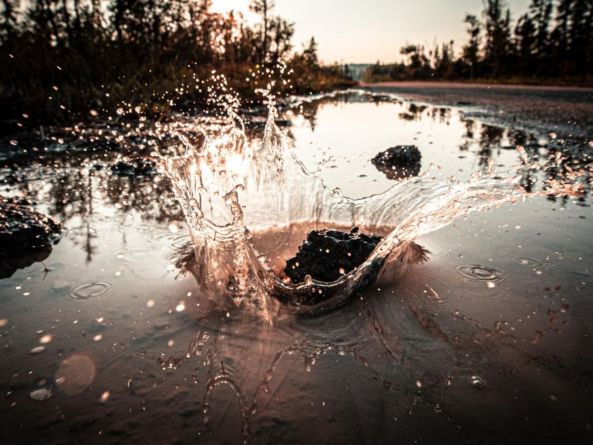 A large rock splashes into a puddle alongside a country road.