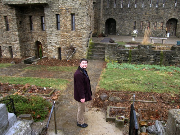 Man stands in the small courtyard near a castle.
