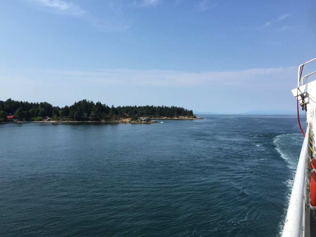 View of a tree-lined coast from the deck of a ferry sailing through the Strait of Georgia.