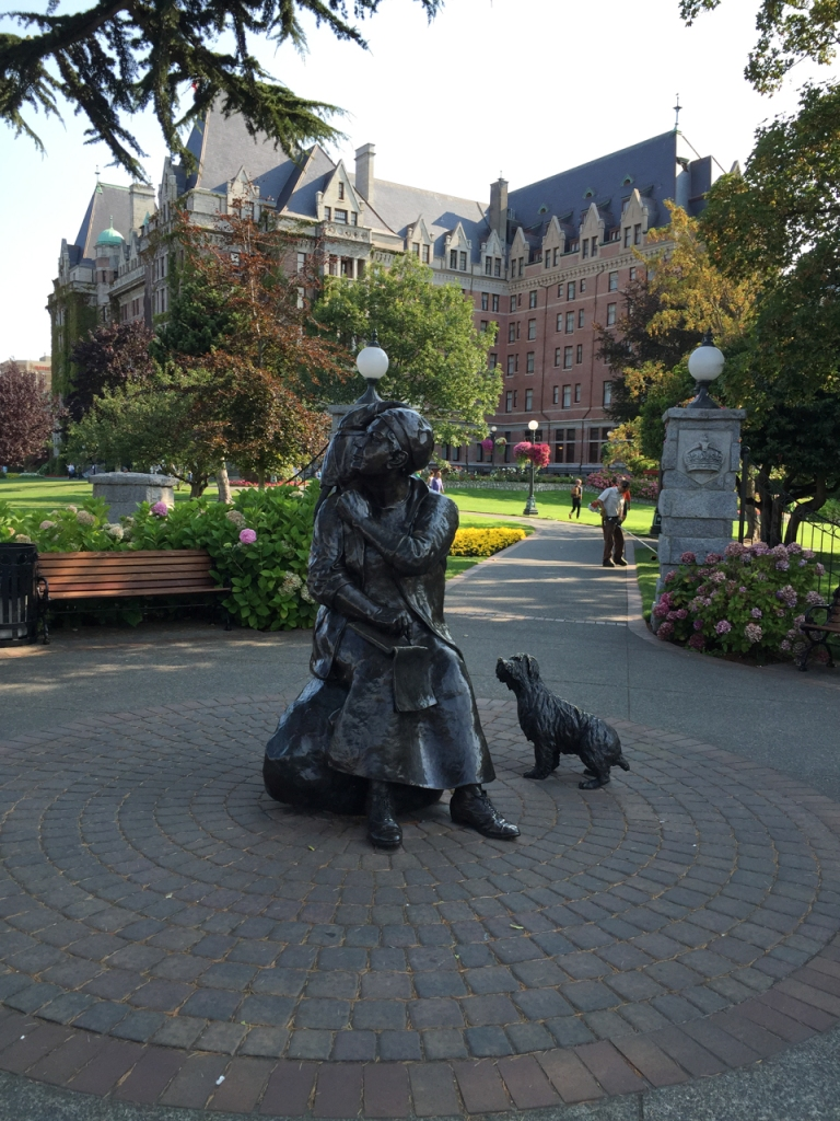 Statue of Emily car seated, with her dog, monkey, and notebook. The Fairmont Empress Hotel stands behind the statue.