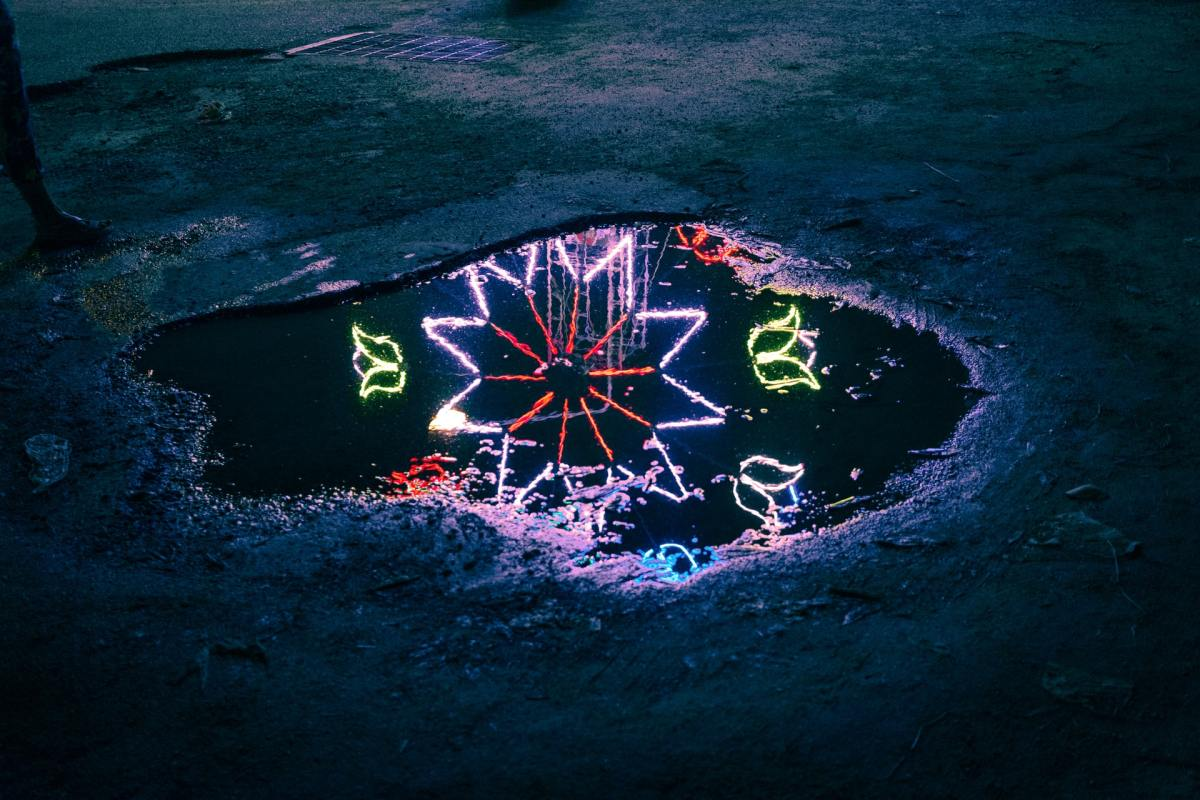 Image of a puddle at night time. Reflected in the puddle are neon lights in the shape of a flower.