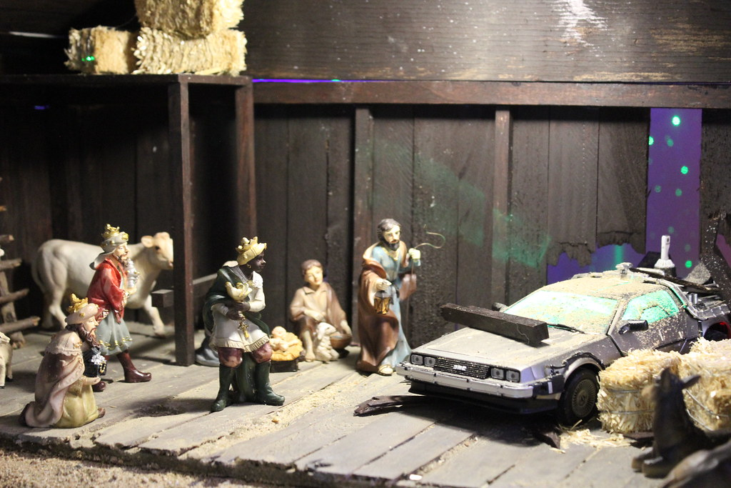 A nativity scene is interrupted by a DeLorean DMC-12, which has crashed through the barn wall.
