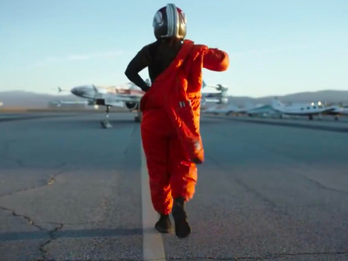 A pilot shrugs on an orange flight suit while walking toward an X-wing fighter.